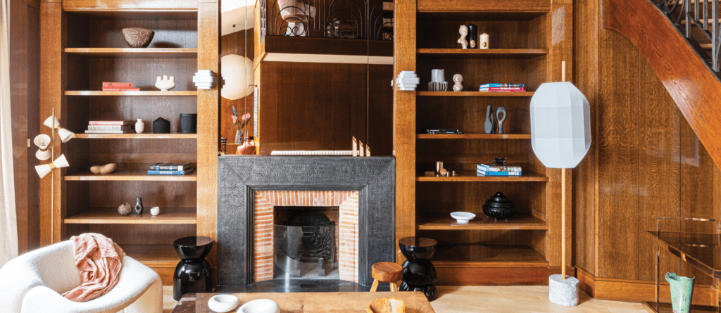 A fireplace surrounded by 1980s-style oak panel walls and a built in bookcase.