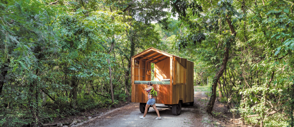Small wooden cabin on wheels.