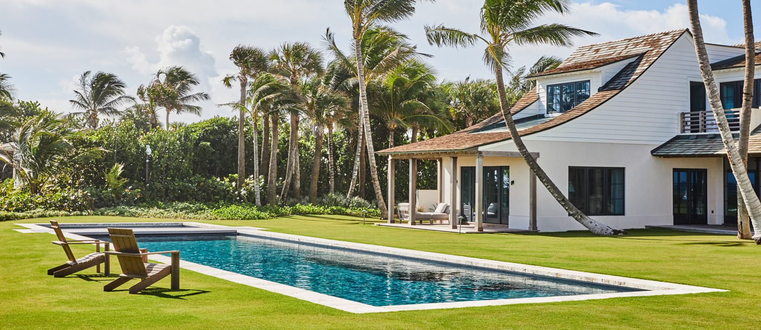 The exterior of a Florida home surrounded by a pool and palm trees by Thomas Melhorn.