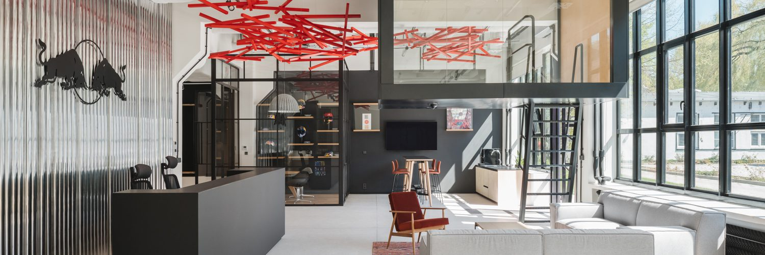 An installation called Wave of Energy swoops above the entrance area in Red Bull's Warsaw offices, designed by MXCF Architekci.