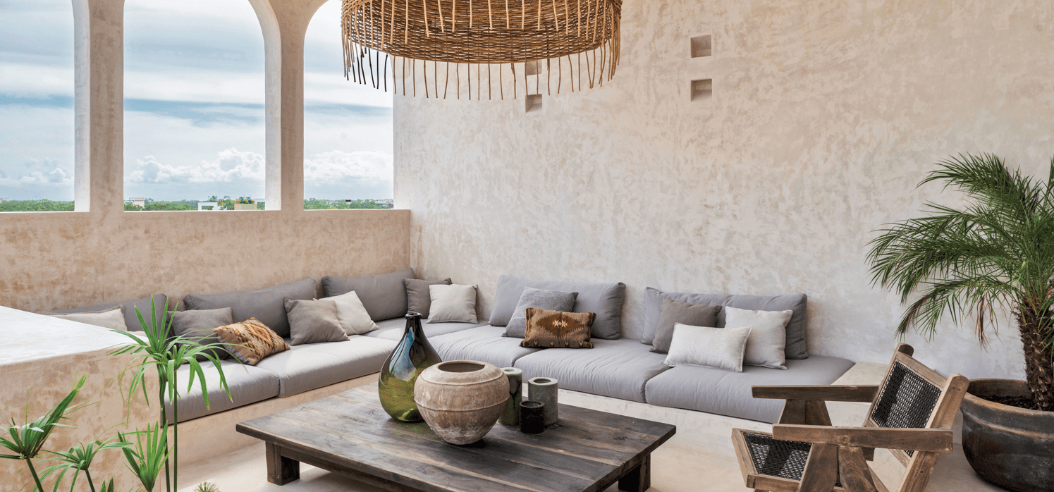 Sitting room with low sofa and open windows with textured sand walls and natural lighting.