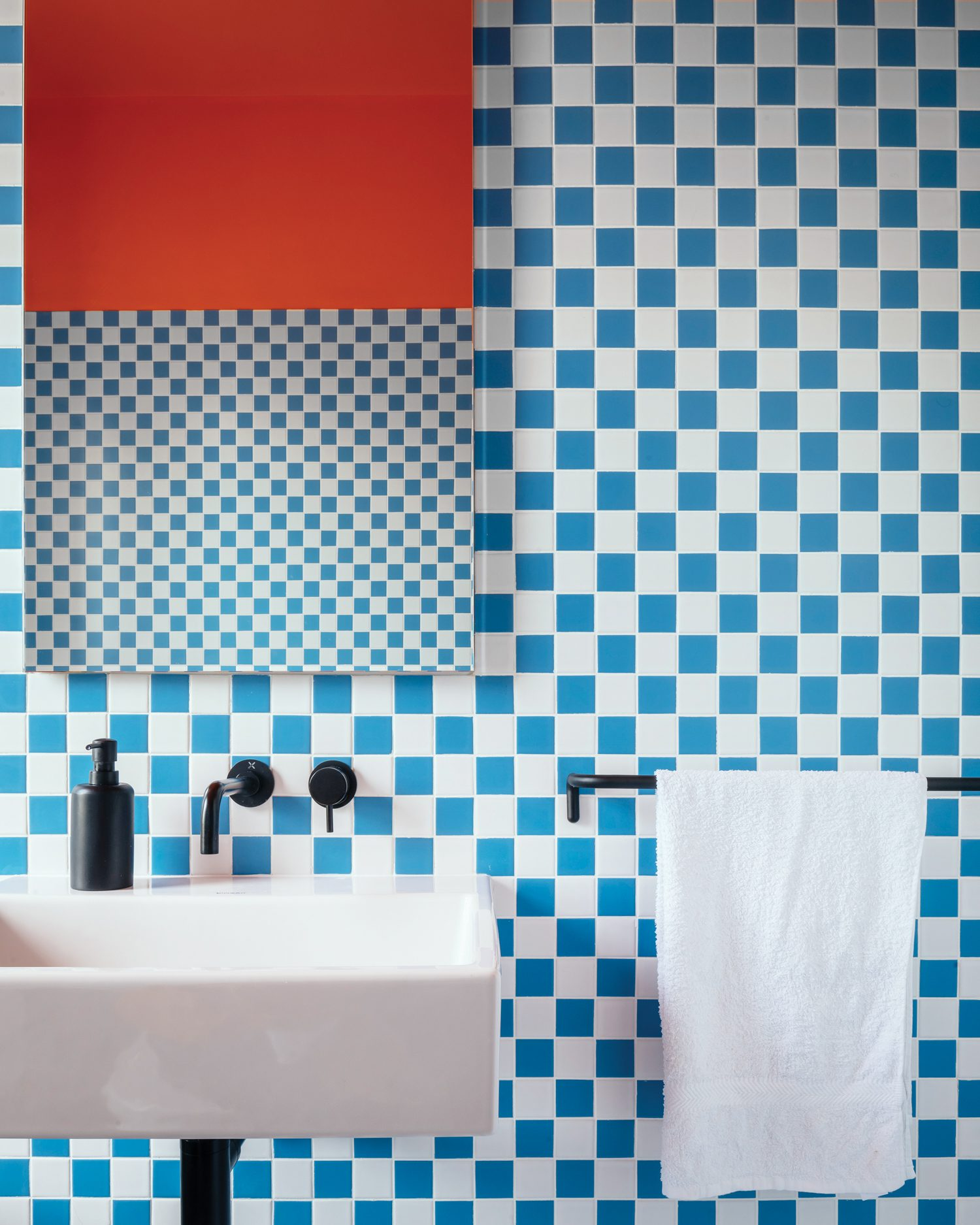 Bathroom tile tips the hat to the original blue-and-white checkerboard uncovered on the main bedroom hearth.