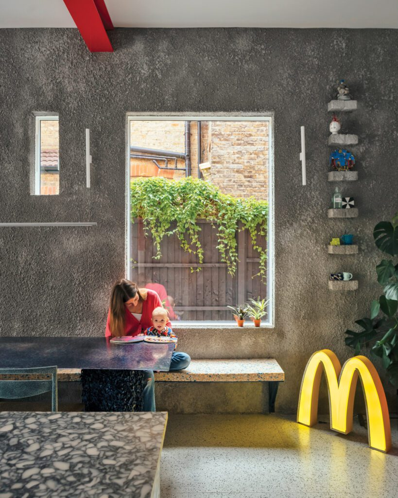 Barnes converted the kitchen's former side door into a window and coated the surrounding wall in roughcast, a rocklike plaster; the McDonald's sign was an eBay find.