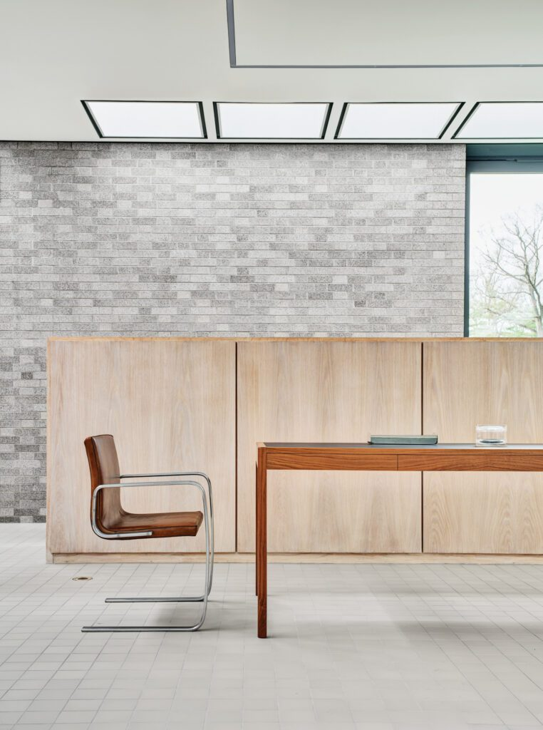 """Poul Kjaerholm's 1974 armchair, from the collection of New York gallery R & Company for """"Modern in Your Life: Design and Art at the Schlumberger Building,"""" and a BassamFellows CB-311 leather desk in a meeting area, with restored skylights. Photography by Michael Biondo."""