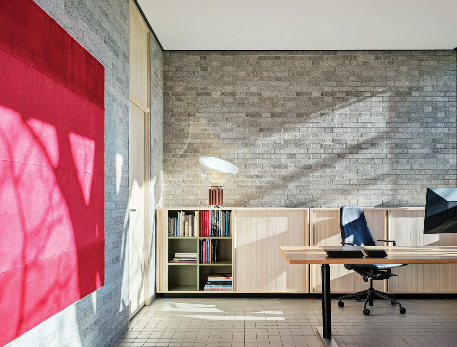 An office's original bricks, cleaned to show their iron-rich glazing, and new French quarry floor tile. Photography by Michael Biondo.