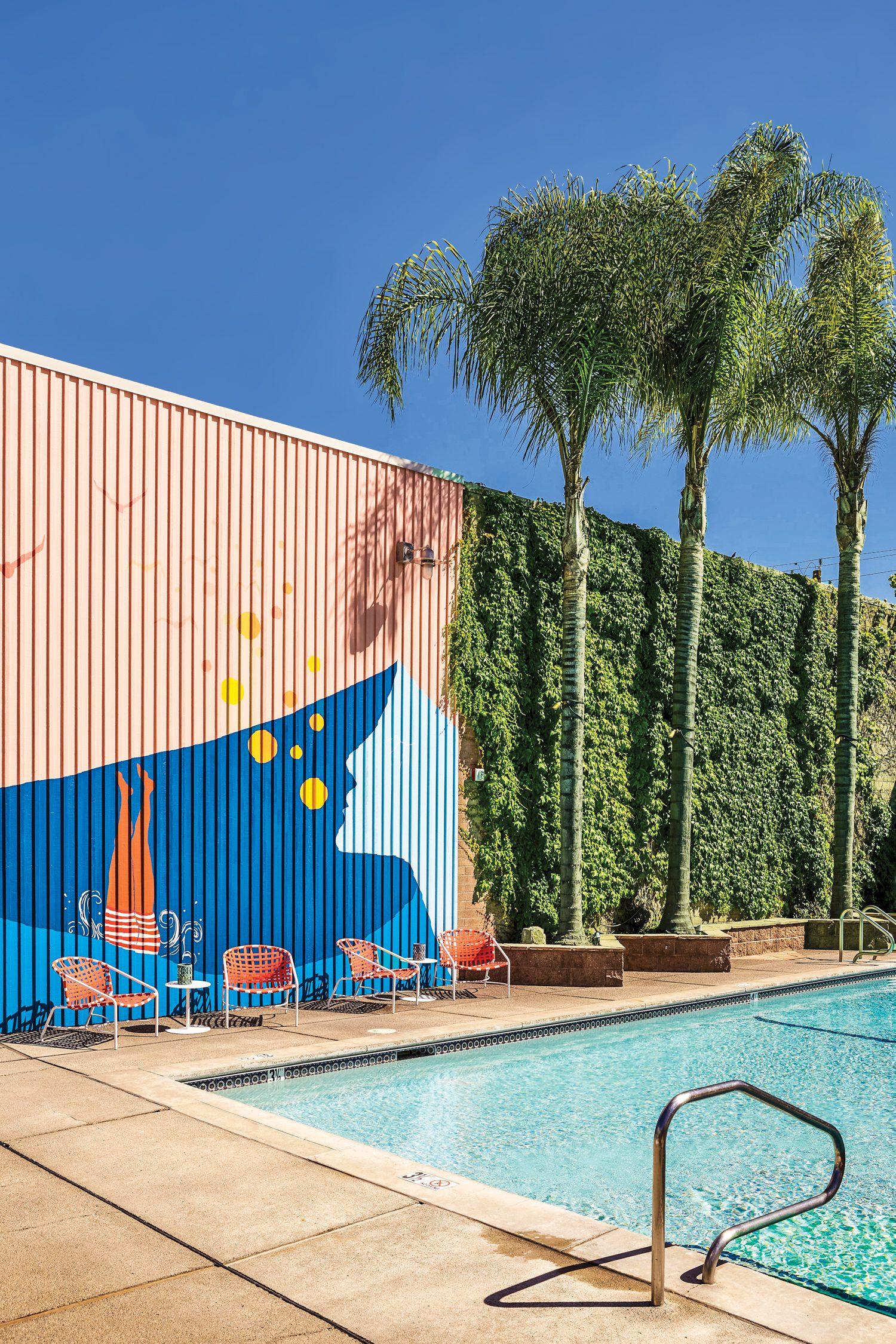 Truth to Paper's 20-foot-tall mural, Brown Jordan's Kantan lounge chairs by Tadao Inouye, and Drops side tables from Janus et Cie update one of three pools at Dr. Wilkinson's Backyard Resort & Mineral Springs, which first opened in Calistoga, California, in 1952, and has been recently renovated by EDGInterior Architecture + Design andSB Architects.