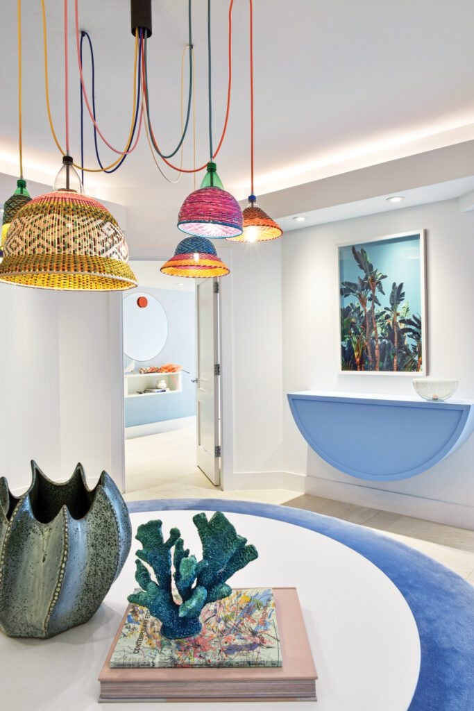 The entryway's PET lamps provide a full range of vibrant color, while an ombré rug and console, both custom, soften the octagonal space; Ludwig Favre's Hollywood Wildlife graces the walls.
