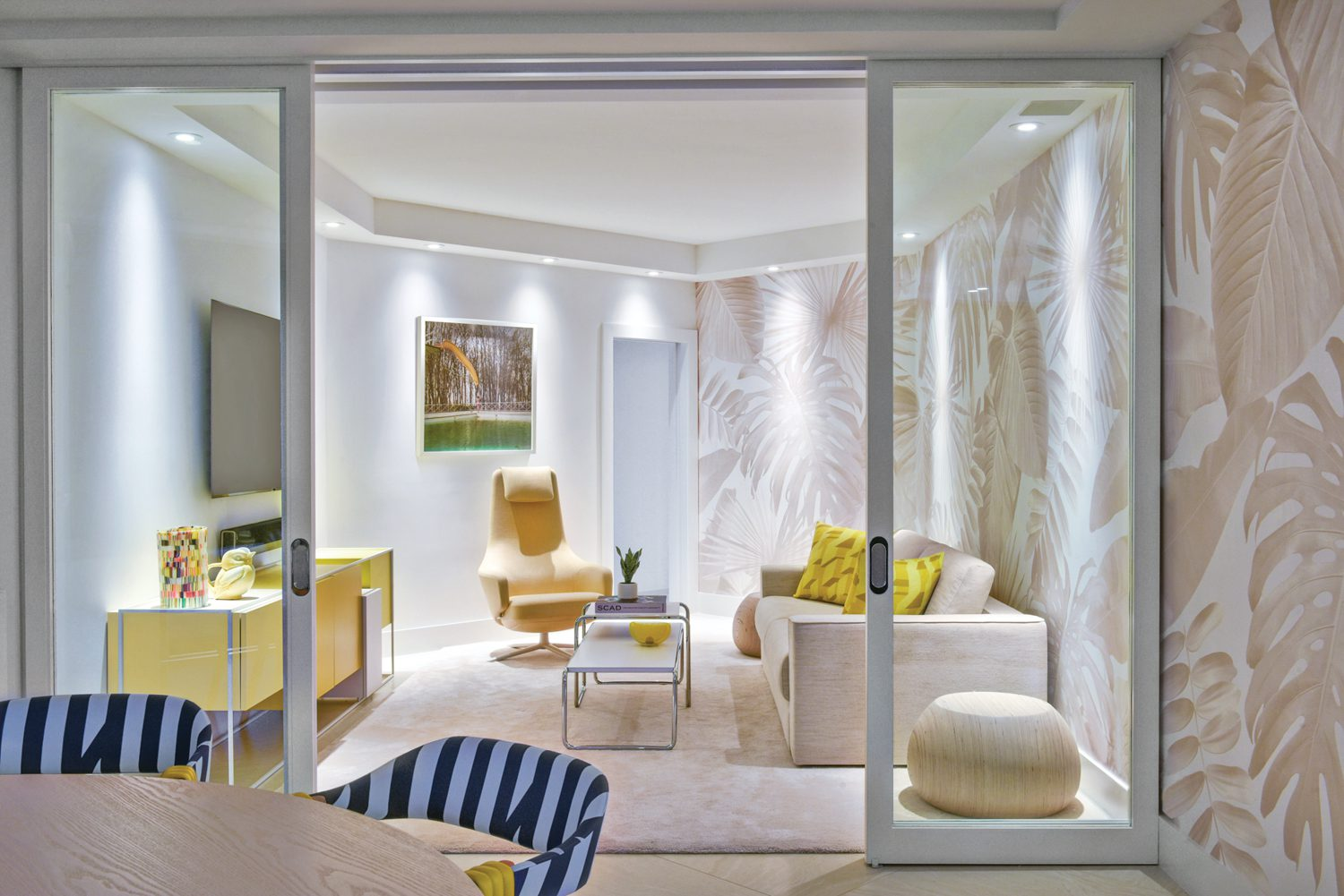 Adjacent to the dining area, a cozy media lounge cordoned off behind sliding glass doors features Antonio Citterio's Repos lounge and Yellow Slide, by Annelie Vandendael.