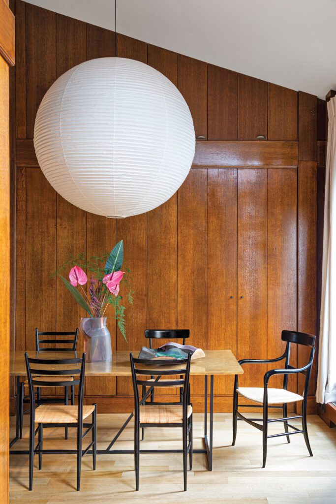An Isamu Noguchi paper pendant brightens the dining room, where the homeowners sit on Fratelli Levaggi–crafted Chiavari chairs; Services Généraux designed the resin vase.
