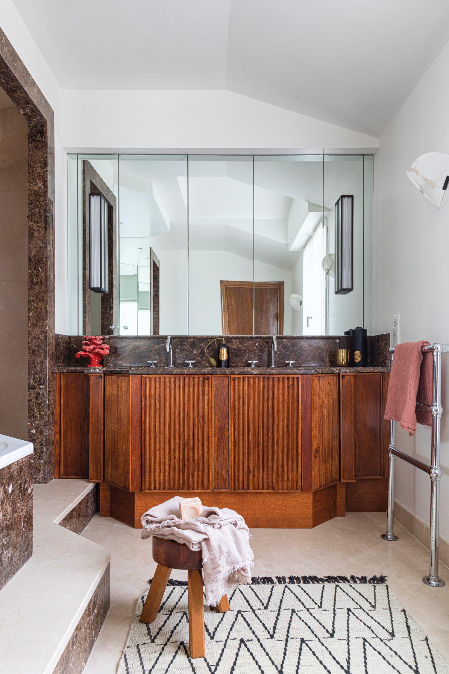 In the primary bathroom, Emperador marble tops the custom vanity of striated oak; the pine stool is by Andreas Martin-Löf Arkitekter.