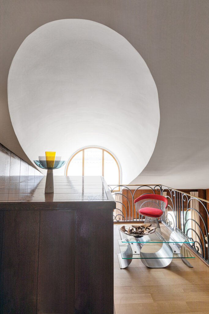A vintage Michel Boyer coffee table and Warren Platner chair echo the curly brass banister of the mezzanine, which also hosts the building's elevator shaft.