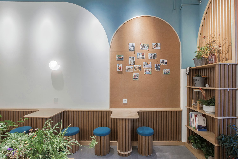 Corkboard creates a photo gallery near custom shelving of paper tubes.
