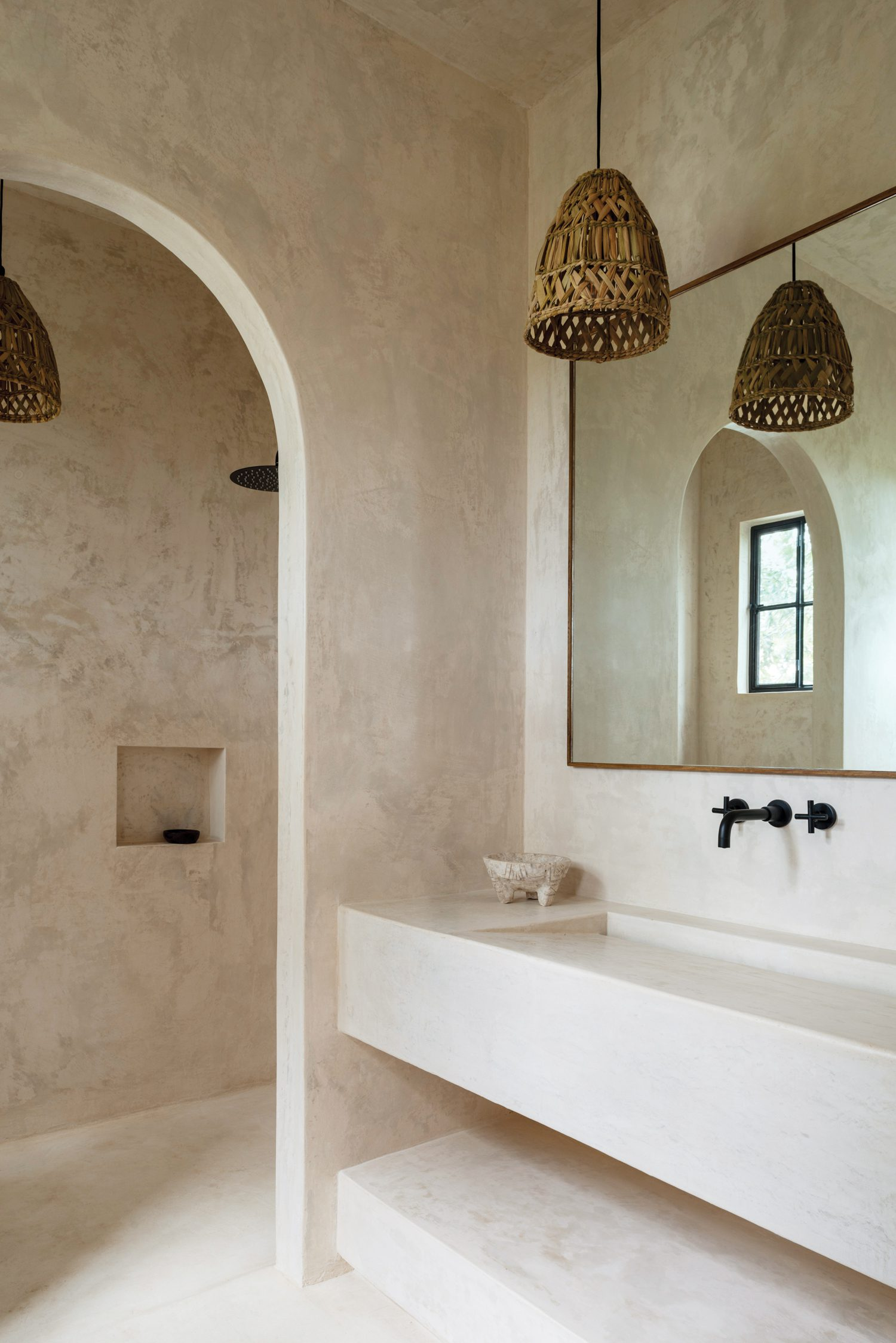 The bathroom walls and integral vanity are also plastered in chukum stucco; the mortar on the countertop is a classical design sourced from a Mayan village.
