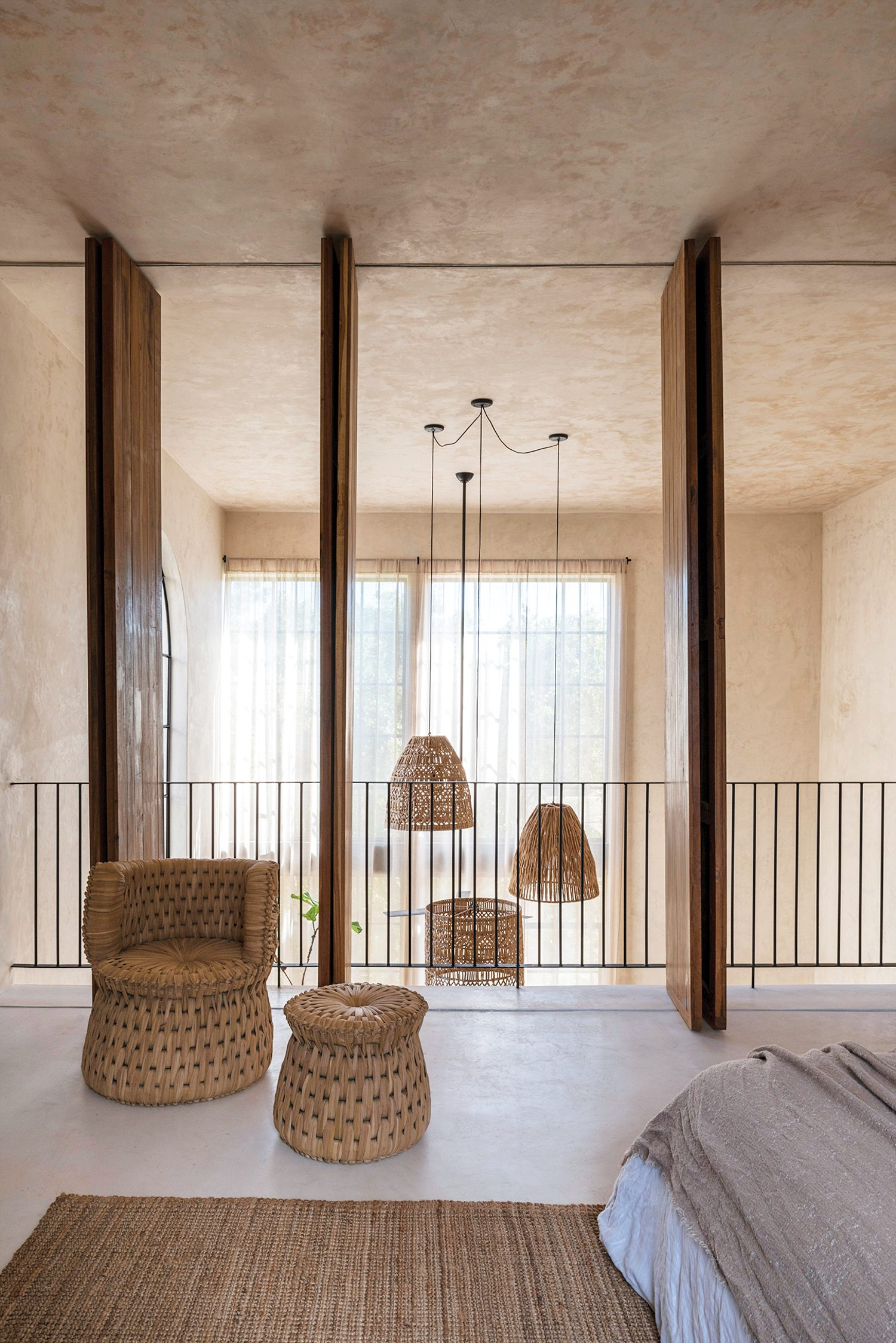 The penthouse's mezzanine bedroom overlooks the living area below but can be closed off for privacy via wooden panels; the chair and lamp are crafted of woven palm.