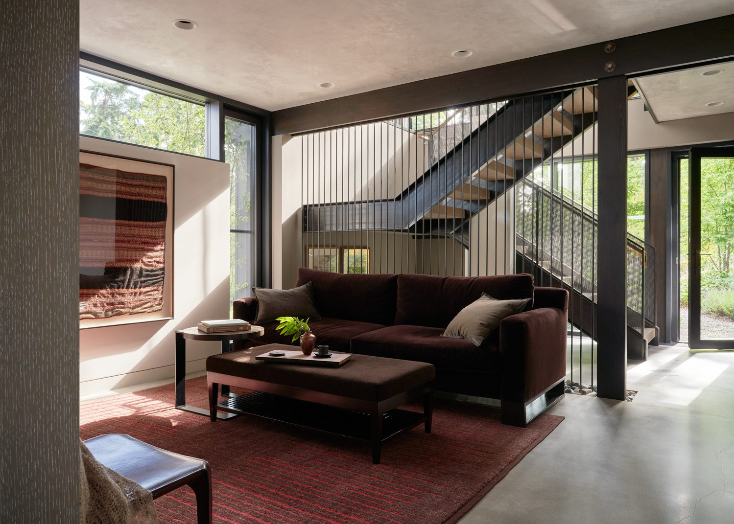 The home's previous maze of small rooms was transformed into an open great room with a new stair leading to a lower-level primary suite, replacing an underutilized garage.