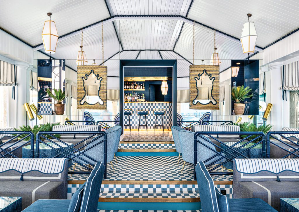 In Cascais, Portugal, Viterbo Interior Design outfitted the bar at the beachfront Hotel Albatroz in Bert & May ceramic tile, Farrow & Ball paint, and custom furnishings, including a pair of wicker-surround hanging mirrors.