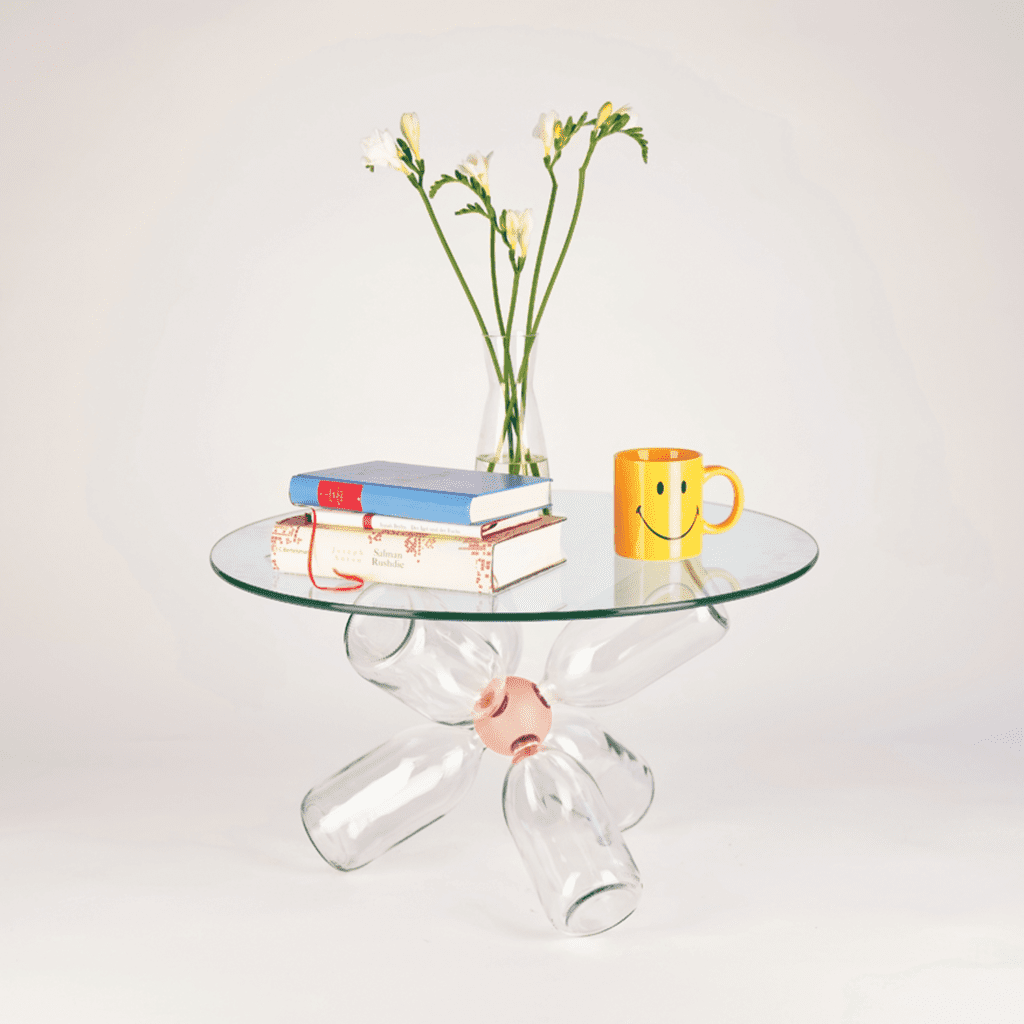 Clear Bang glass-top table with base of upcycled glass bottles adjoined via painted wood and nylon connector in Pastel Rose by Buster Bang.