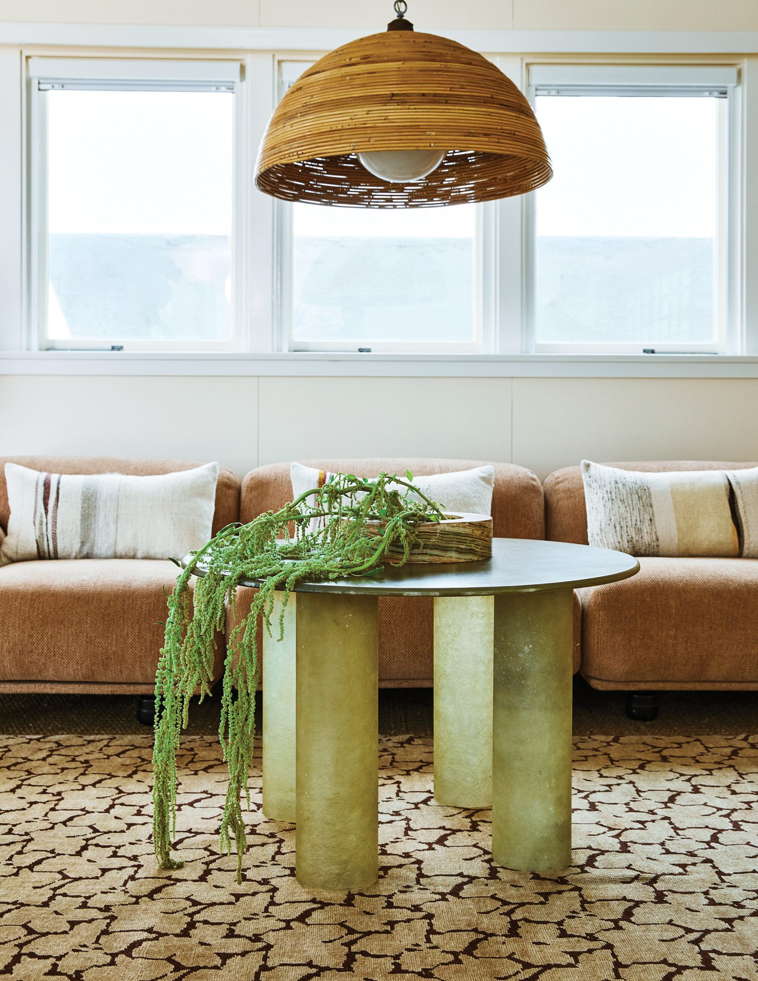 In the den, a fiberglass table by Aschberg Magnuson pairs with a pendant original to the house.