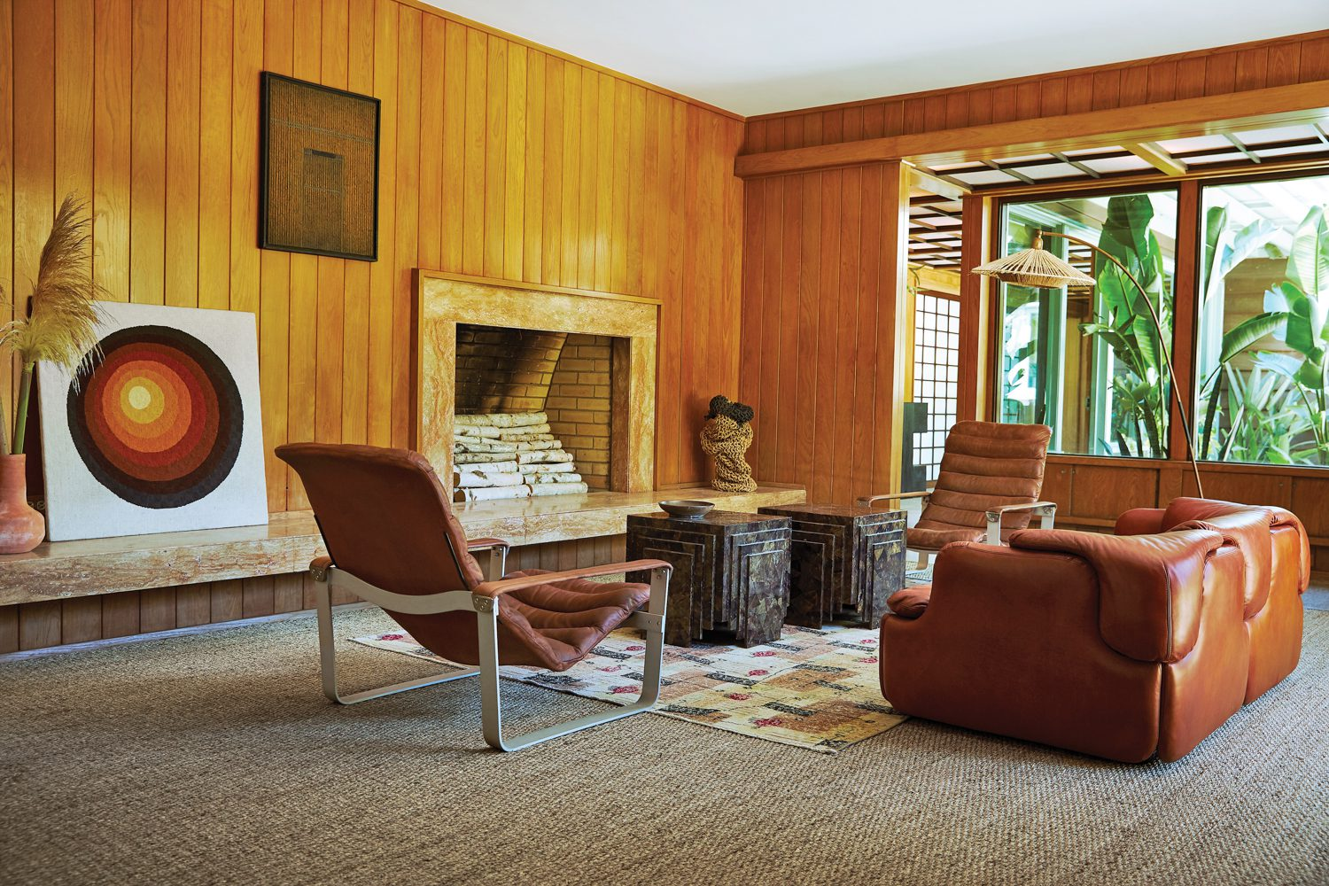 The family room's main seating vignette features unique finds like tortoise shell coffee tables and 1968 Pulkka lounge chairs by Ilmari Lappalainen.