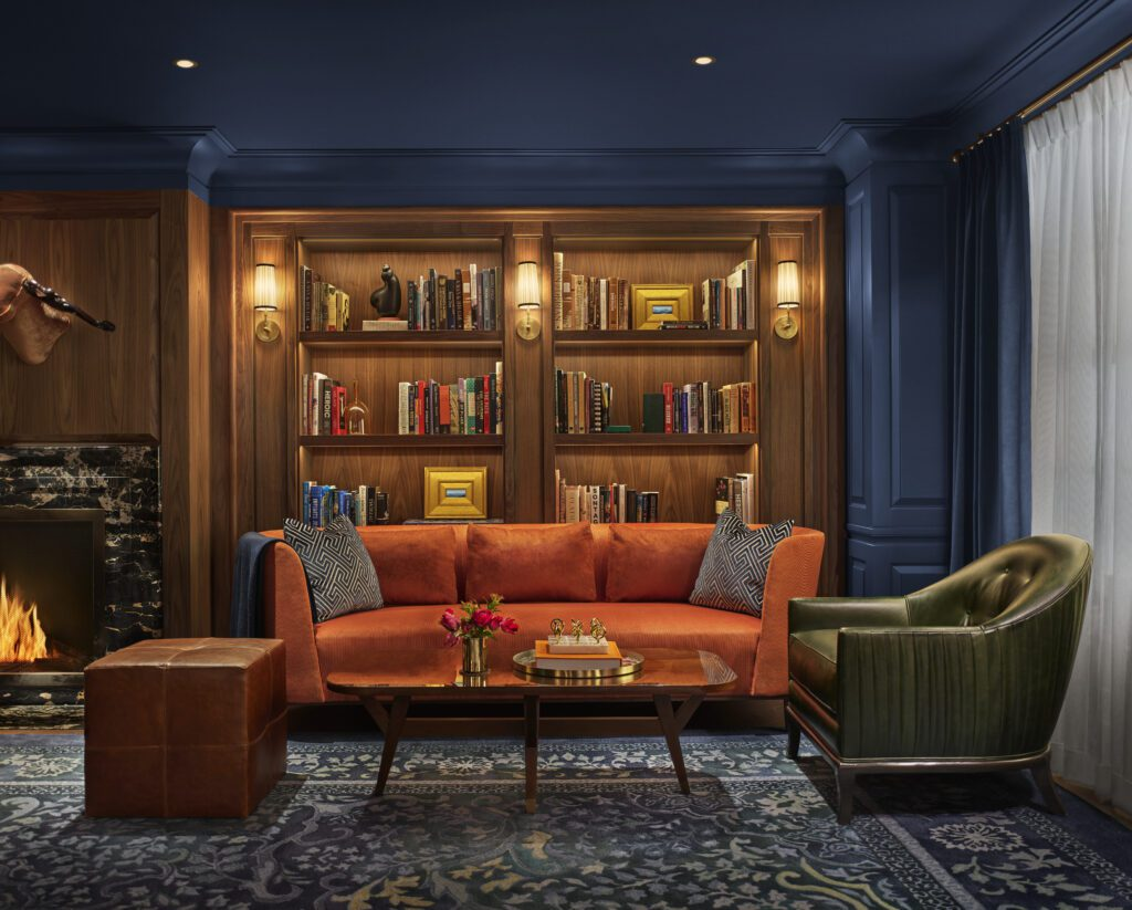 In the private library lounge of the Newbury Boston hotel, recently renovated by Jeffrey Beers International, Champalimaud Design, and Ken Fulk, a rediscovered fireplace blazes next to a curated collection of books. Photography by Nikolas Koenig.