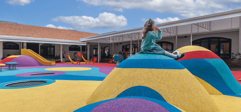 Child sitting on top of a colorful mound in a school playground.
