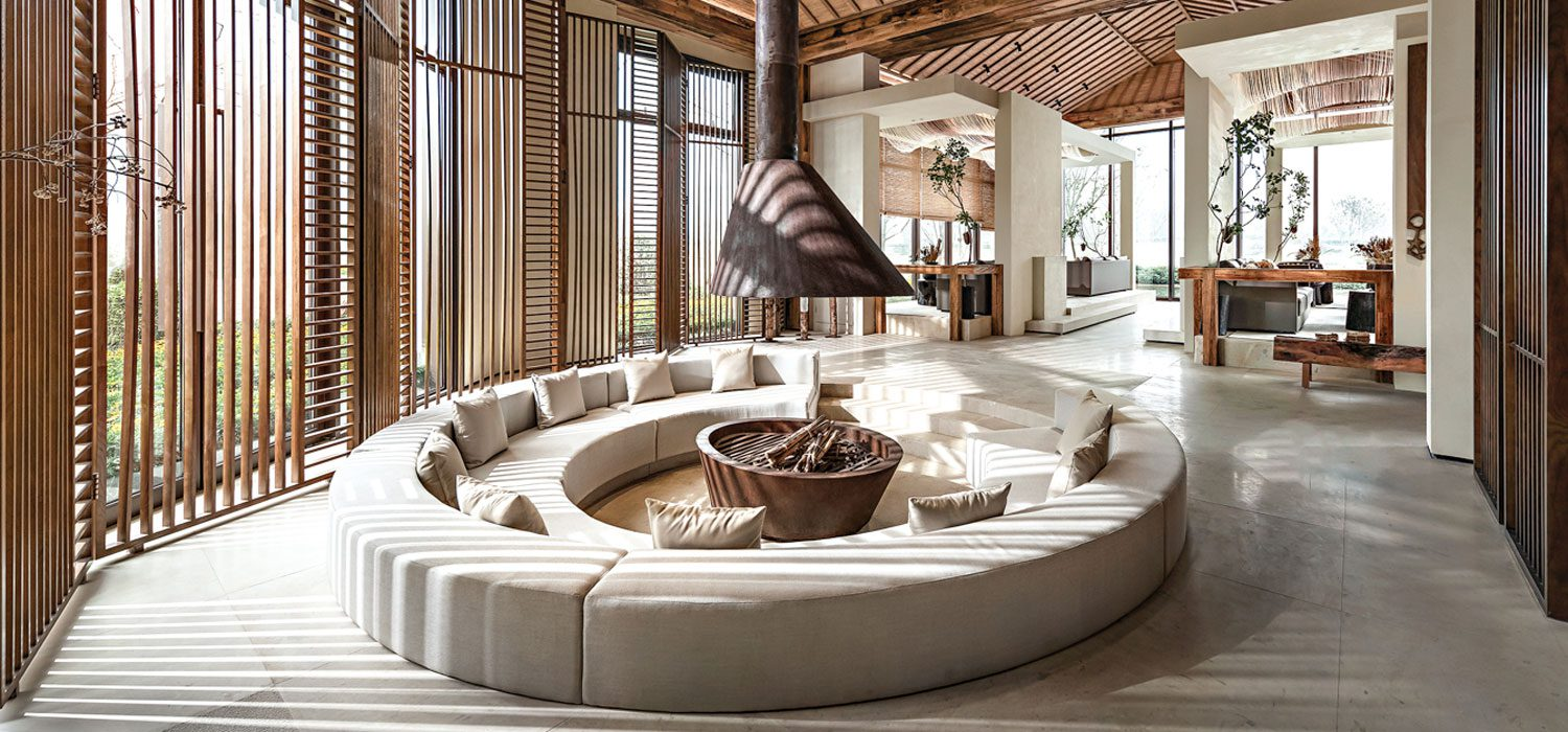 A firepit is surrounded by a circular couch.
