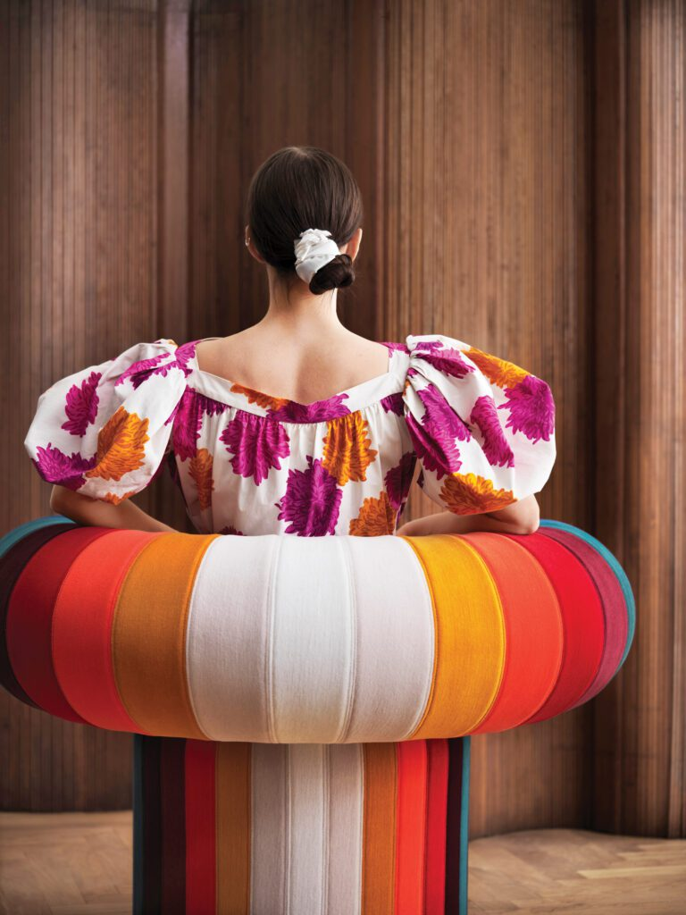 Big Talk, Adam Goodrum Studio's semicircular throne for Blå Station, pictured here, is a rounded arm chair decorated with vertical stripes in blue, shades of red, gold and white. A woman sits in the chair with her back to the camera.