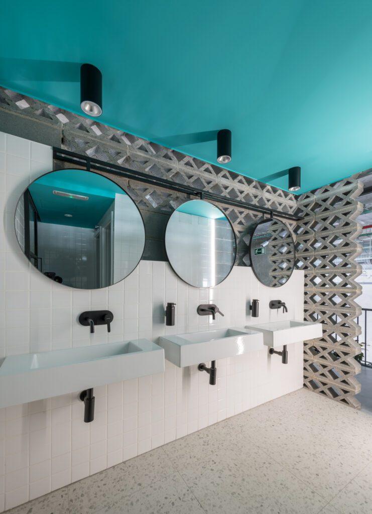 Breezeblocks create a privacy screen in a brightly-colored bathroom.