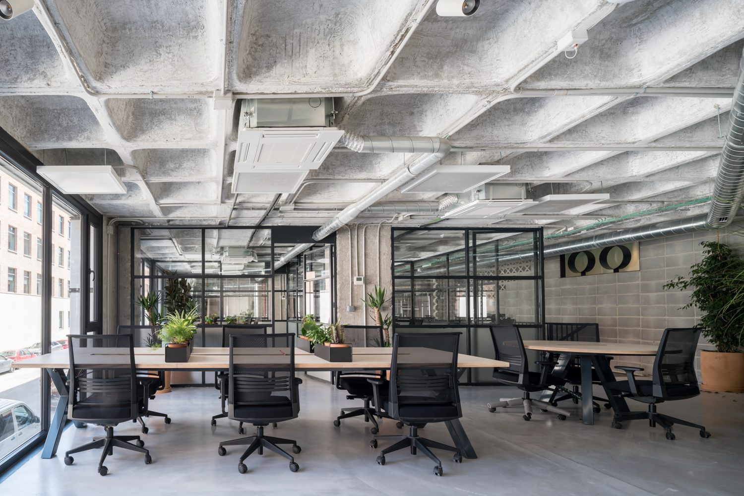Concrete ceilings and glass partitions organize the office areas.
