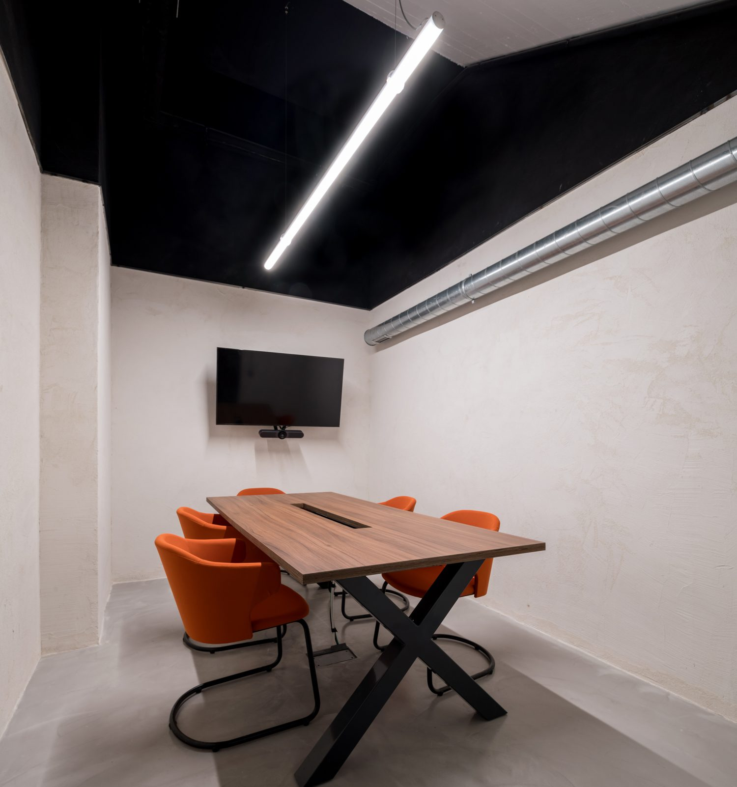 In a conference room, the simplicity of linear light fixtures and cross-beam tables keep the focus on the meeting.