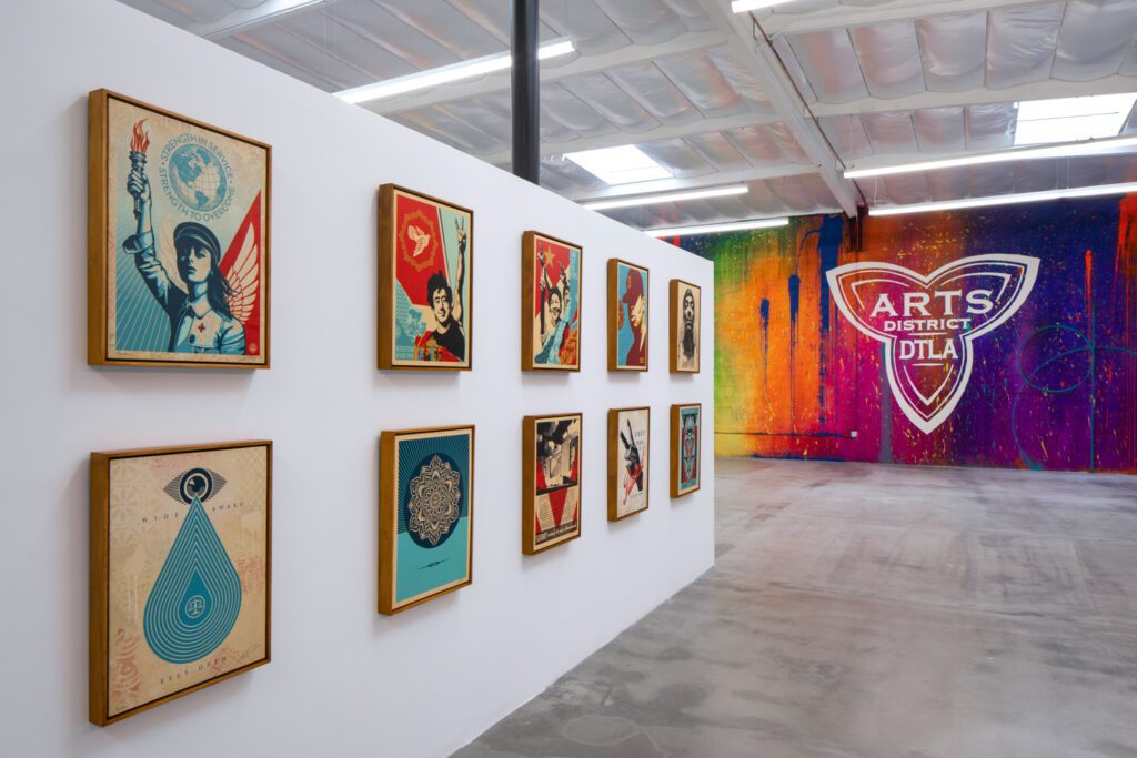 At left, prints by Fairey; mural by Risk with DTLA arts logo by Damon Martin.