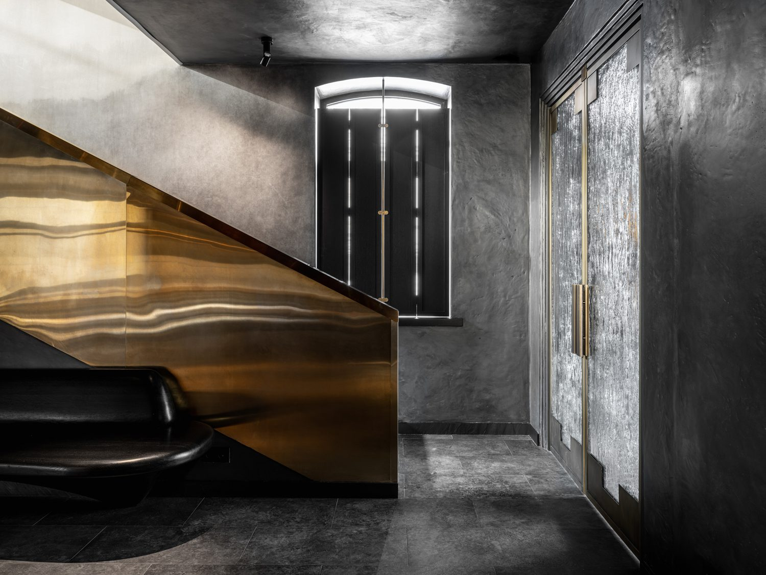 A staircase layered with brass sheets unites the two floors.