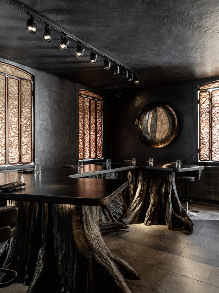 A 10-seat chef's table seemingly sprouts from the earth, with a base constructed of fallen, pickled, and polished tree stumps from the North Caucasus and a slab of wild pear for a top.