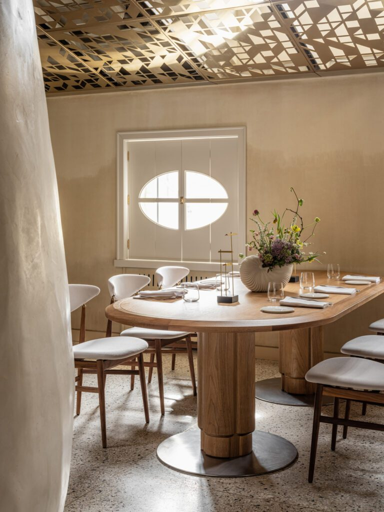 Watercolored walls provide texture and dimension to the neutral palette of the custom dining tables and chairs.