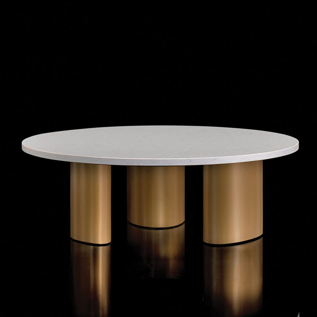 The Marlowe table, which has a white round top and three, thick brass legs is pictured against a black background.