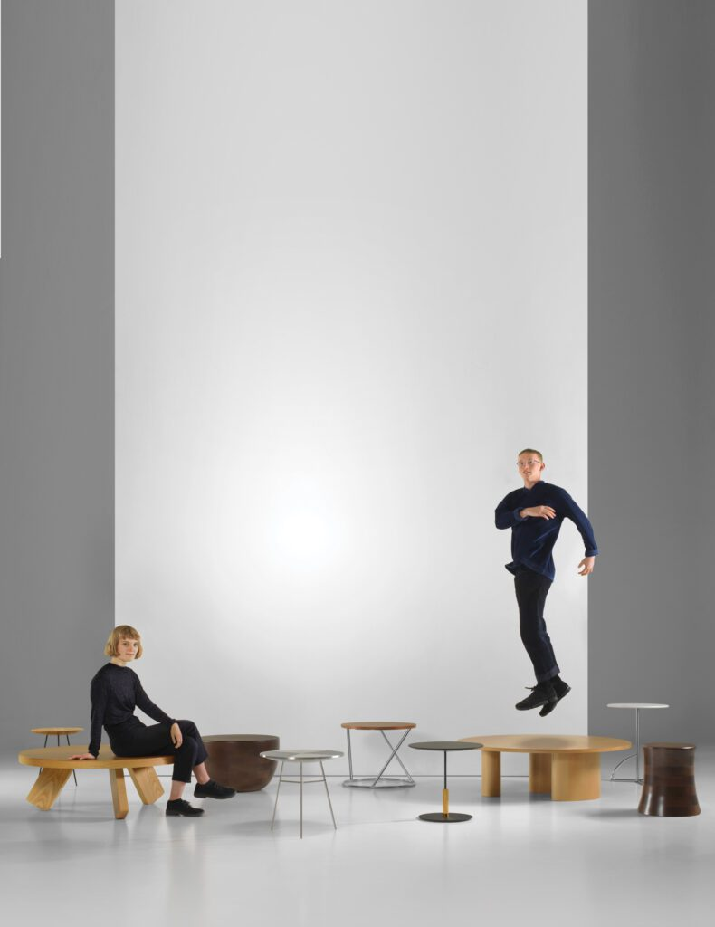 Two designers pose amongst a variety of round tables.