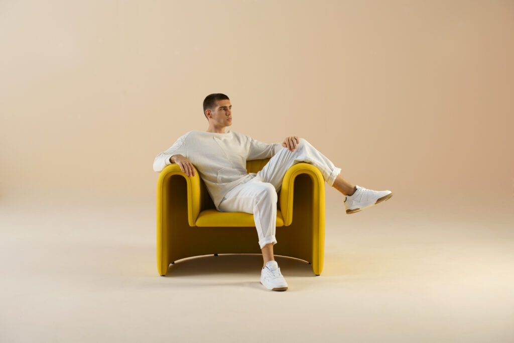 Person sitting in a golden u-shaped armchair.
