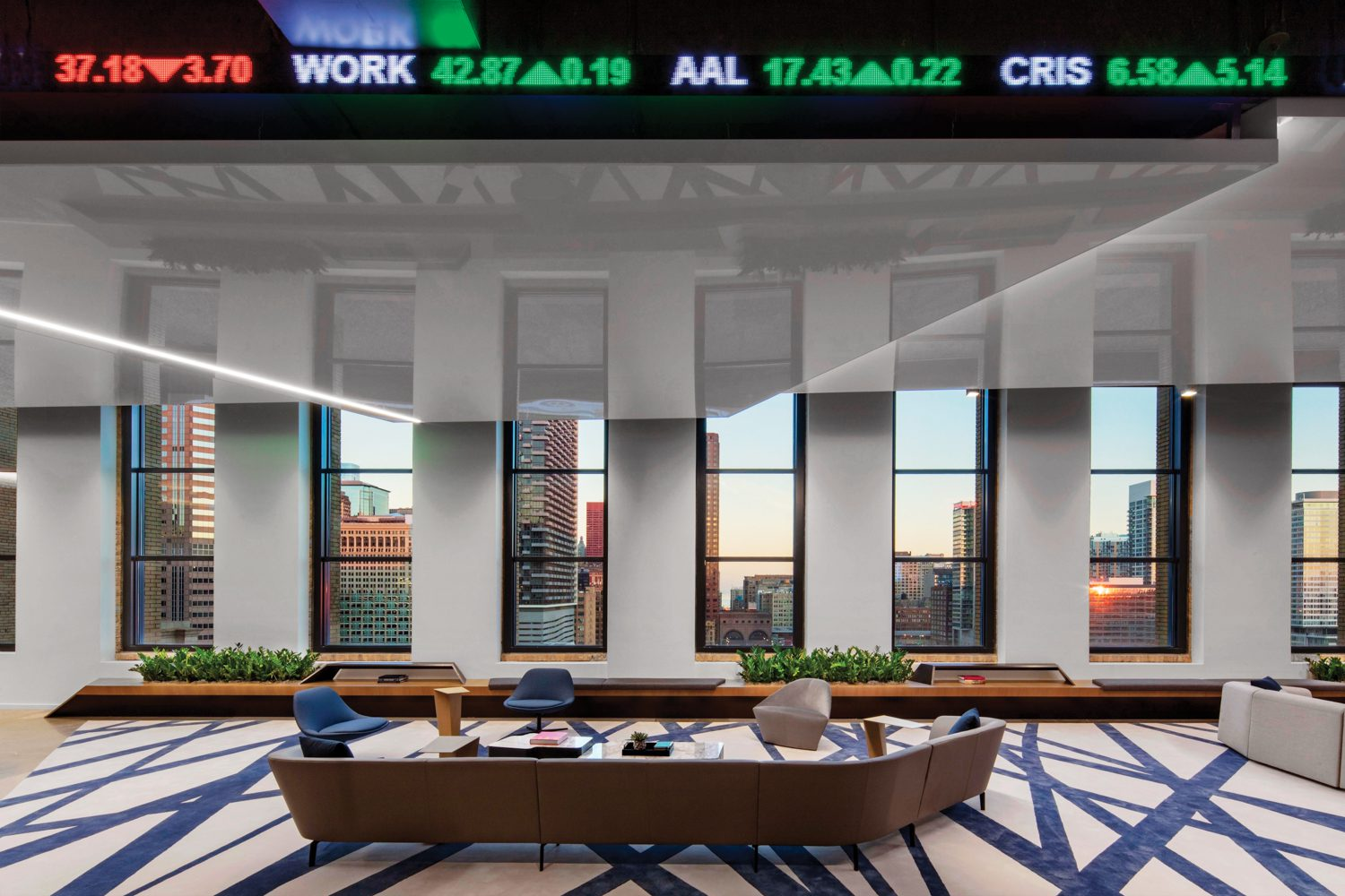 In reception at the Cboe Global Markets headquarters in Chicago by CannonDesign, Lievore Altherr Molina's Loop sofa and Kelly Wearstler's Channels rug introduce the angular concept carried throughout the three-floor office.