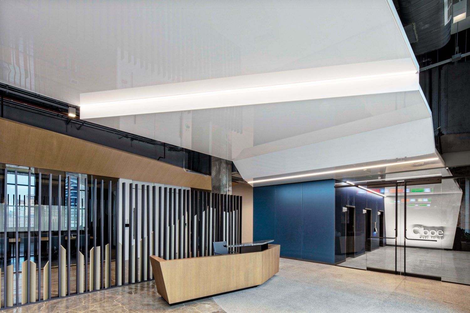 From the elevator lobby, a glossy stretched ceiling and an oak desk backed by a painted metal screen, both custom, welcome staff and visitors to reception.
