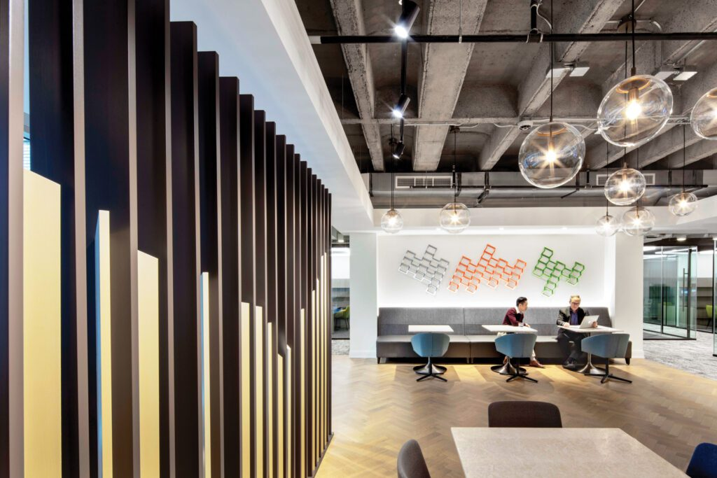 A slatted painted-metal screen similar to reception's flanks the social hub, where the herringbone flooring is white oak.