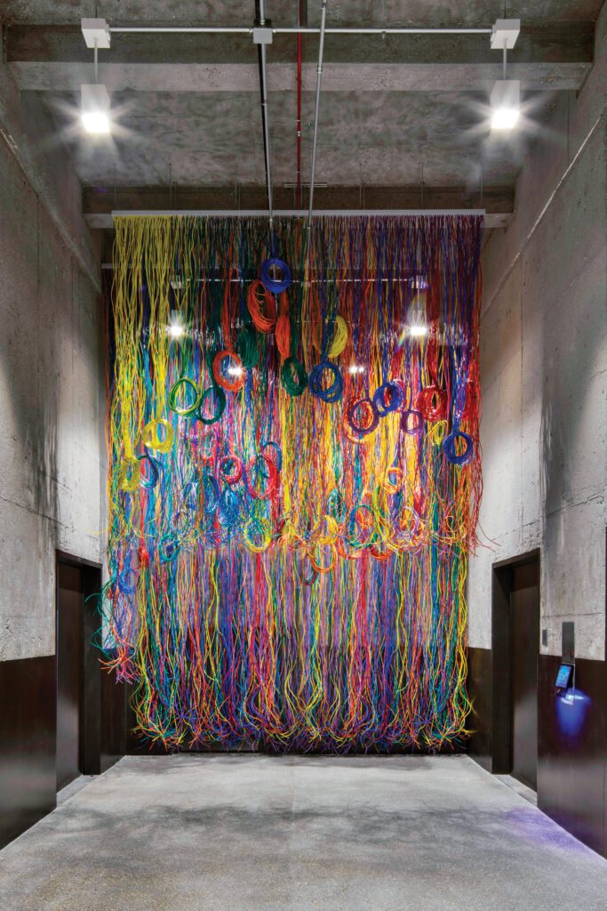 Thousands of feet of colorful cables, some looped, turn the elevator lobby into an homage to the advanced technology that enables electronic trading.