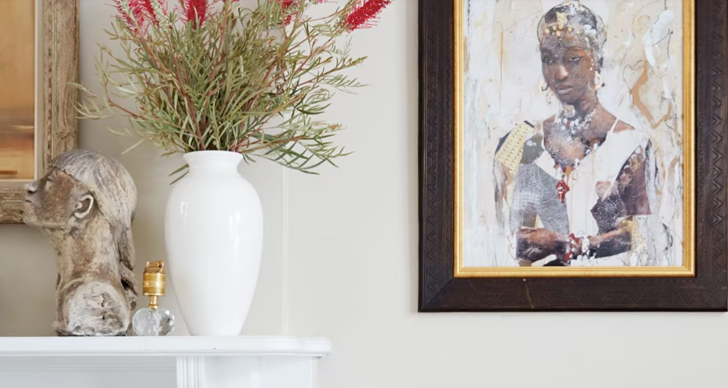 A white wall with a woman's portrait and a floral arrangement on a mantel in the background.