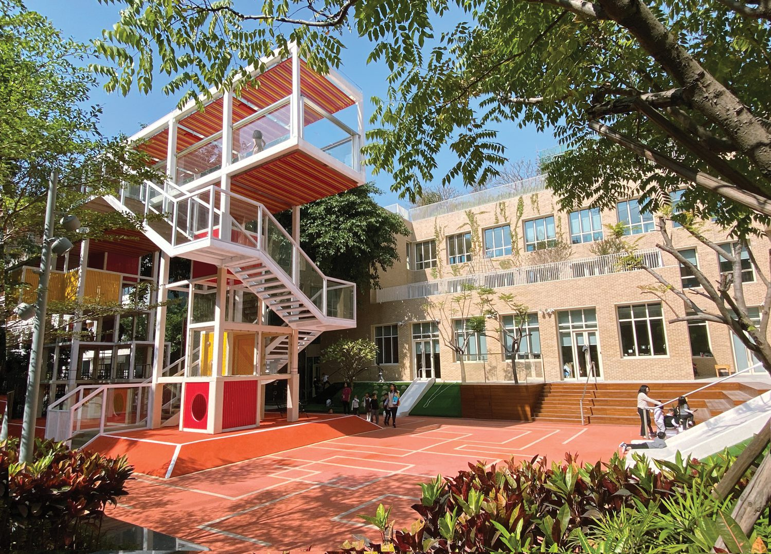 Exterior of school with a red exposed stairwell.