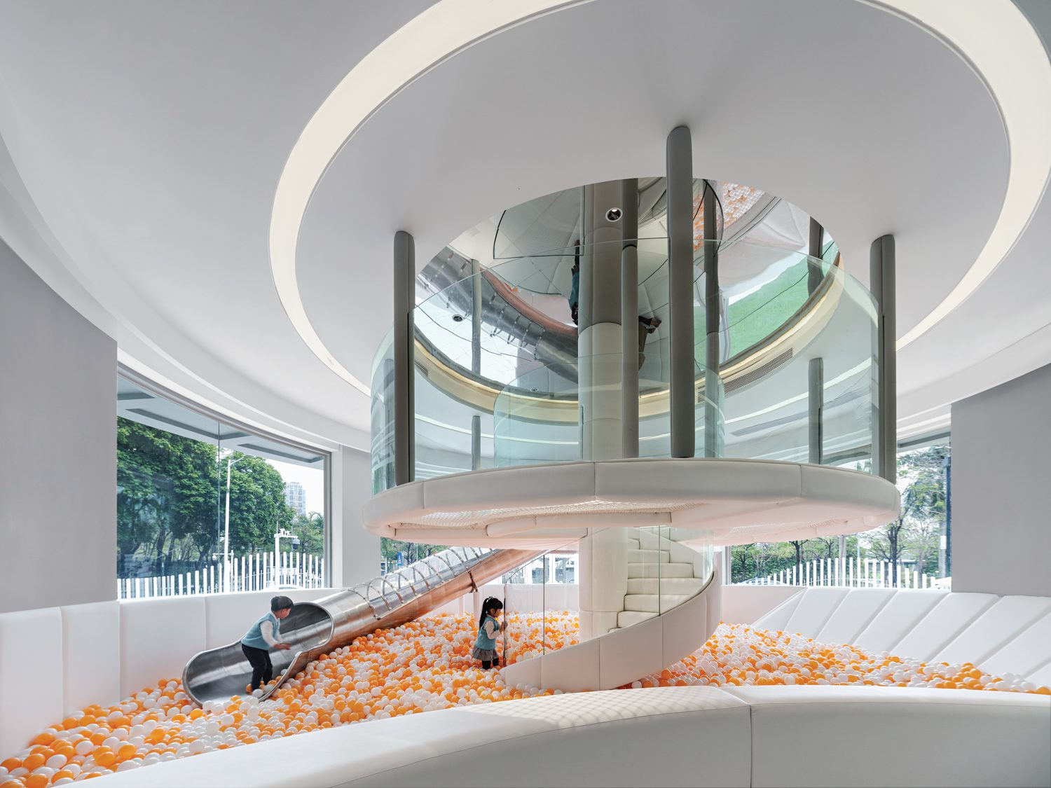 Indoor ball pit with peach colored balls beneath a spiral ceiling.