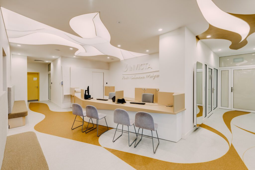 The reception and waiting area at Invicta, a women's fertility specialist and health clinic in Wrocław, Poland, introduces the design's emphasis on curves.