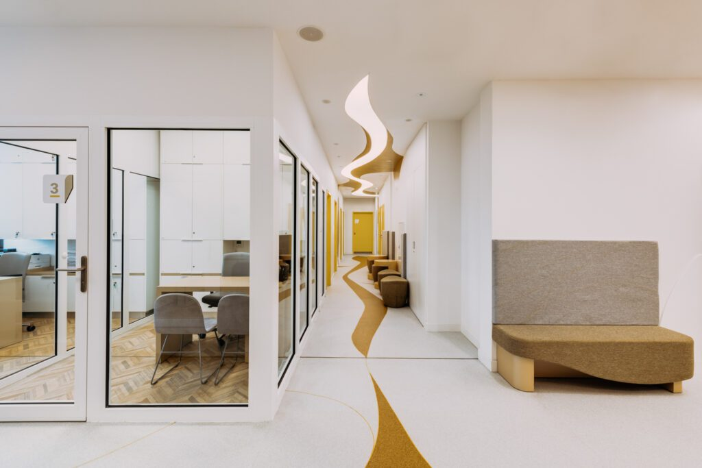 Curved geometry is mirrored in the floor pattern and ceiling in the hallway of the clinic.