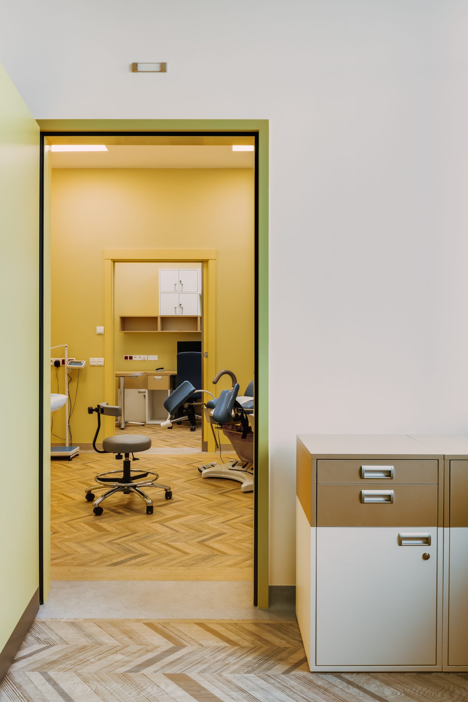Patient treatment rooms have herringbone faux wood floors—actually rendered in homogeneous surfacing by Gerflor.