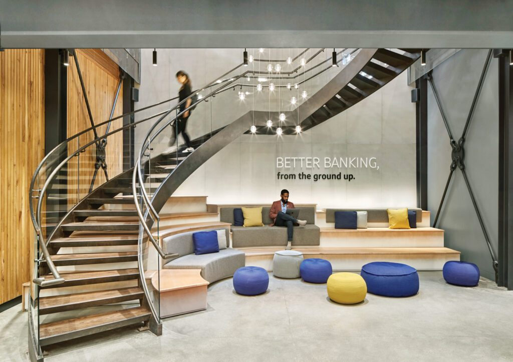 Blue and yellow poofs offer seating below the curved staircase.