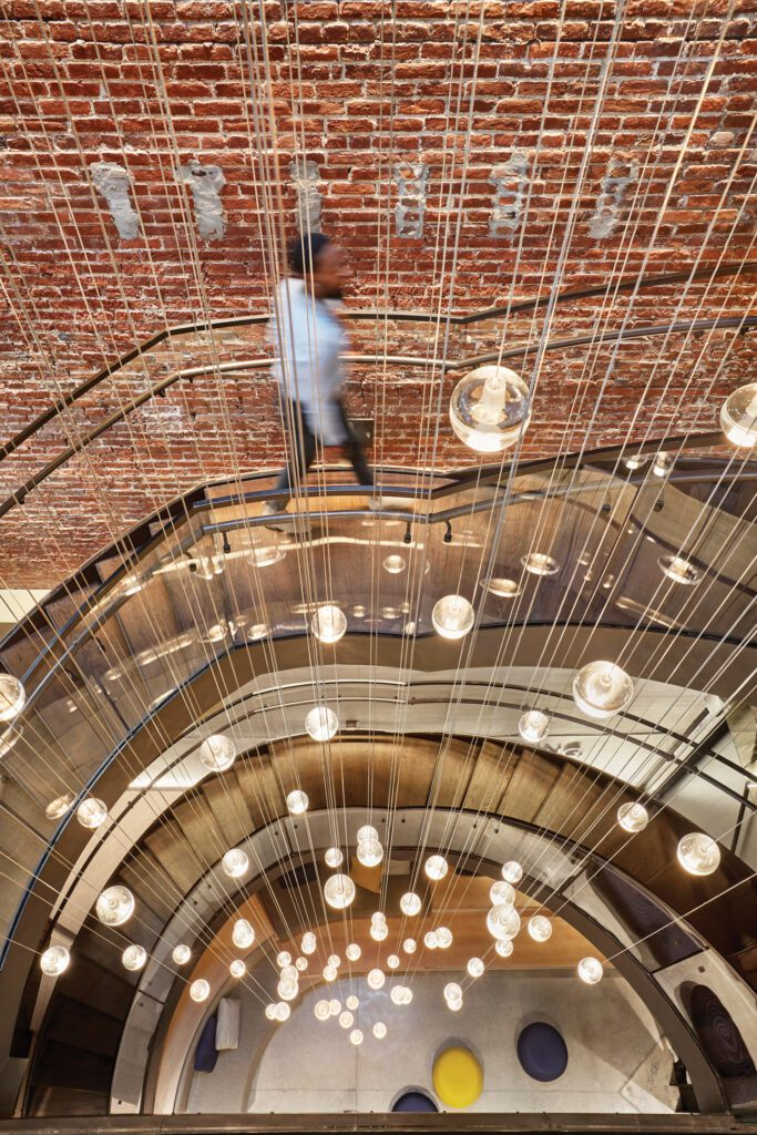 Globe lights suspend from thin wires serving as a centerpiece for the winding stairwell.