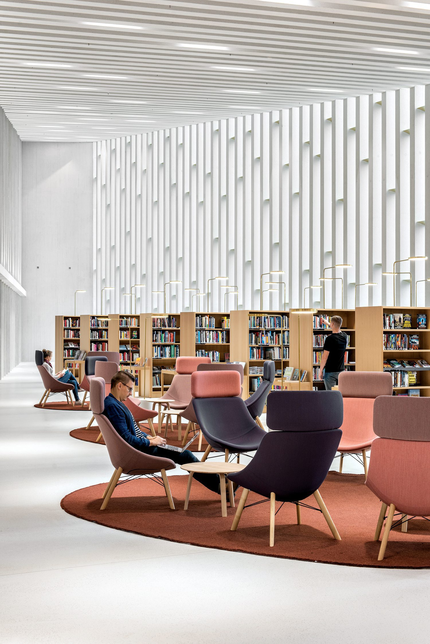 Rust colored circular rugs define seating areas among the wooden shelves filled with books.